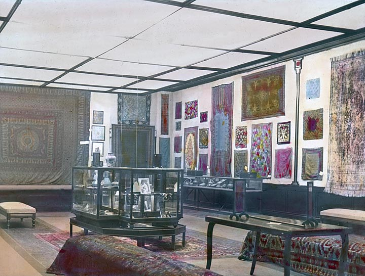 """A hand-colored installation view of the exhibition """"Official Persian Exhibition From Panama-Pacific Exposition, San Francisco"""" held at the Milwaukee Art Institute in January 1916, scanned from a glass lantern slide. Milwaukee Art Museum, Institutional Archives."""