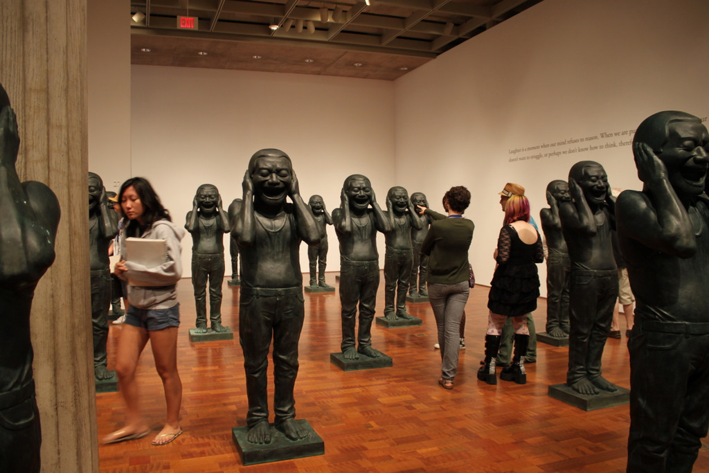 """Teens explore the """"Chinese Contemporary Warriors"""" installation by Yue Minjun."""