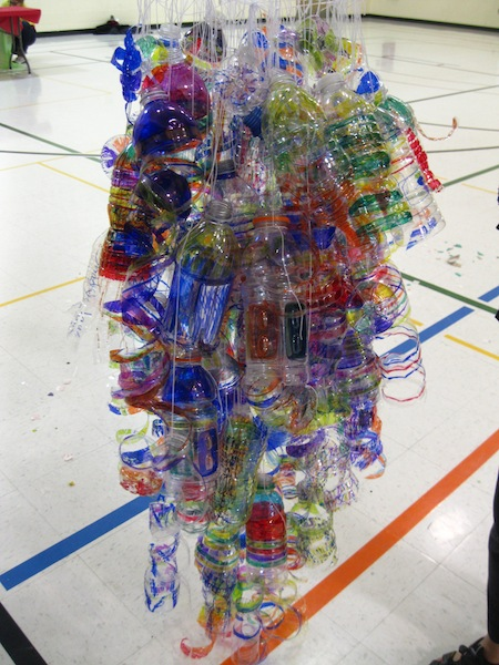As more students add to the sculpture, it grows bigger and fuller until finally, the finished sculpture, made collaboratively, gives a similar, colorful effect to Chihuly's original sculpture.