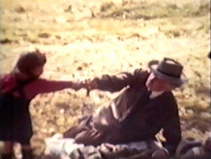 Film still: Frank Lloyd Wright in a friendly tug-o'-war with a child during a picnic outing at Taliesin, late 1930s-early 1940s. Milwaukee Art Museum, Institutional Archives.