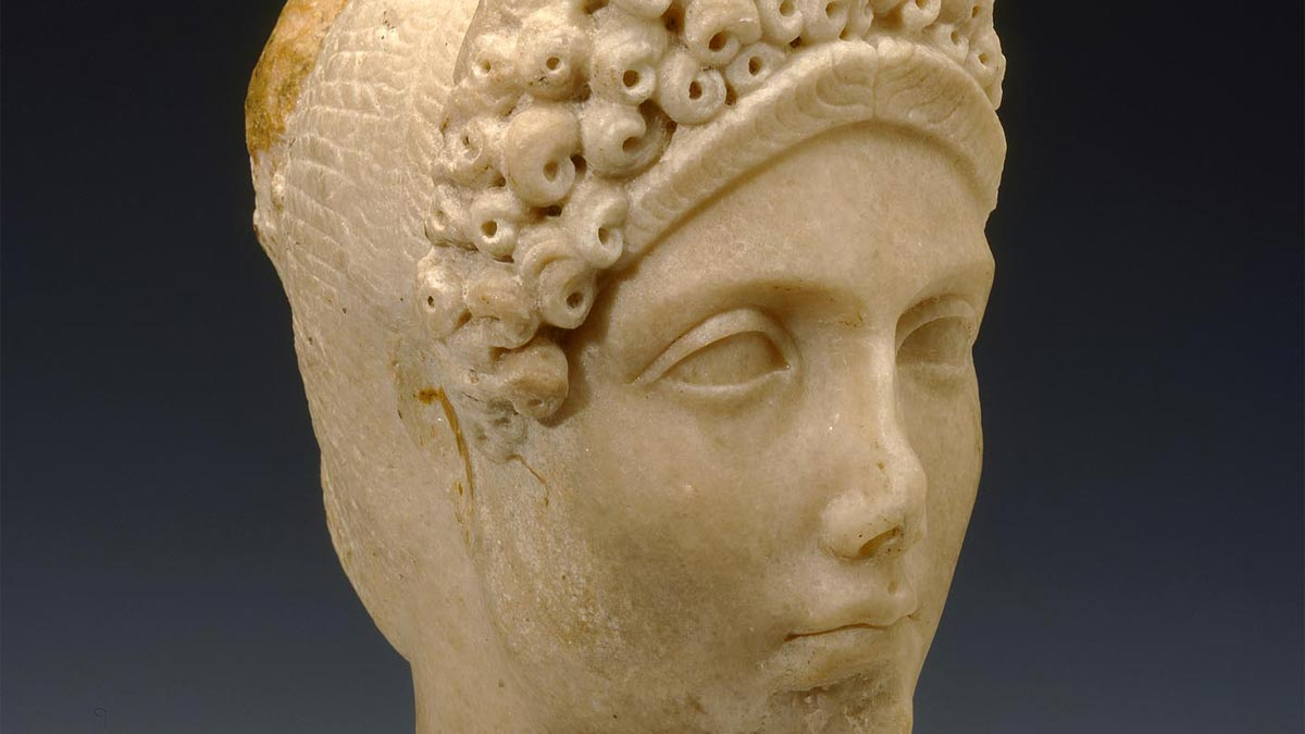 Detail of a bust of a noble woman made of tan marble