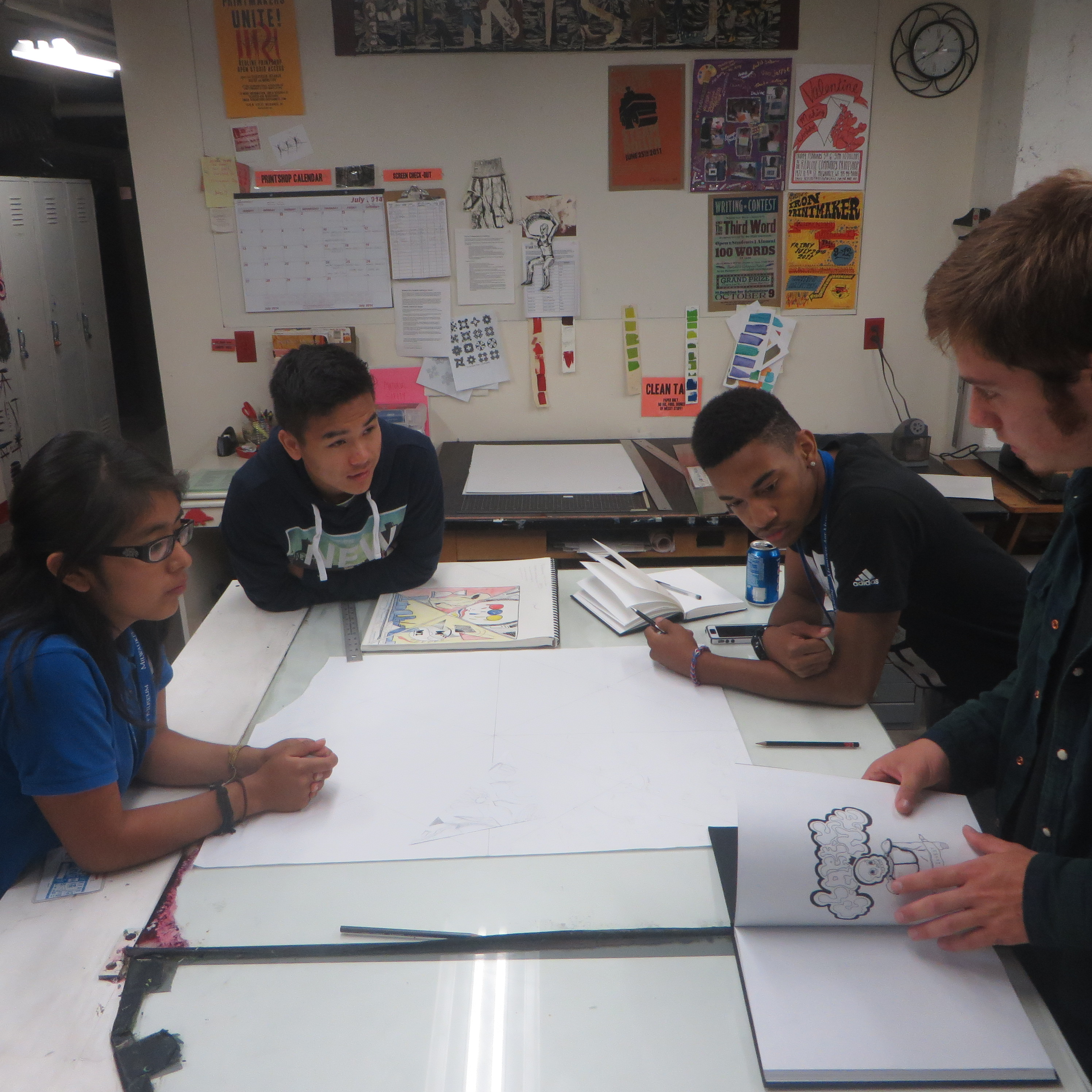 Anaeli, Xai, Diamante, and Clarence discuss ideas for the composition of their portion of the mural. Photo by Jessica Janzer