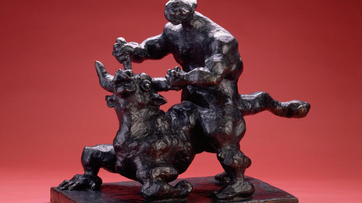 Black sculpture of a man grabbing a minotaur by the horns