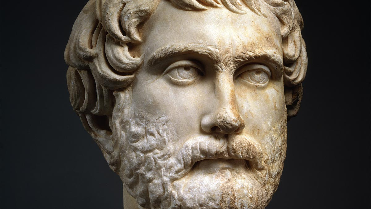 Marble bust of a man with a beard and short curly hair