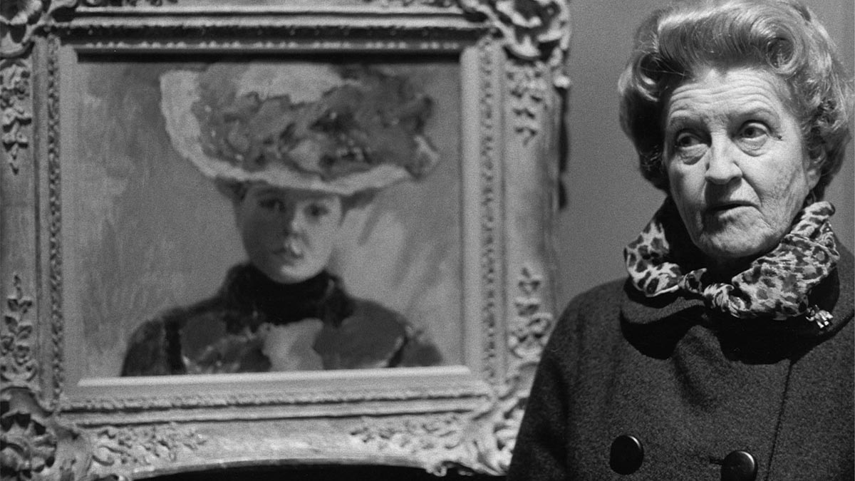 Older woman standing next to a framed work of art