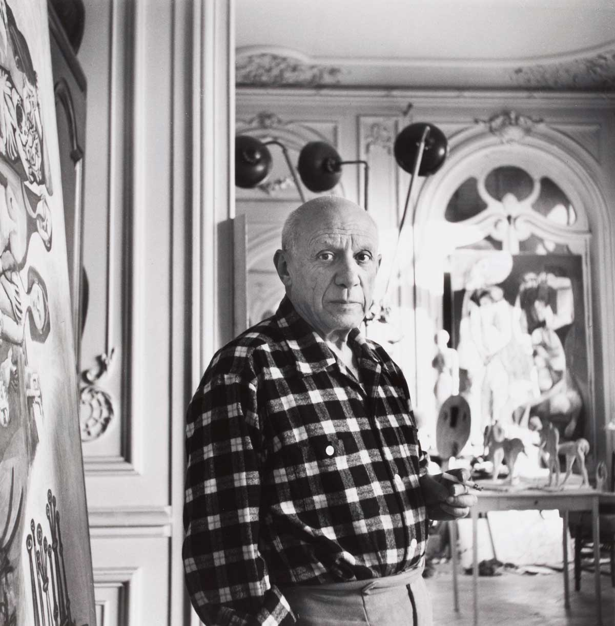 Black and white photo of a man in a checkered shirt standing in an entryway