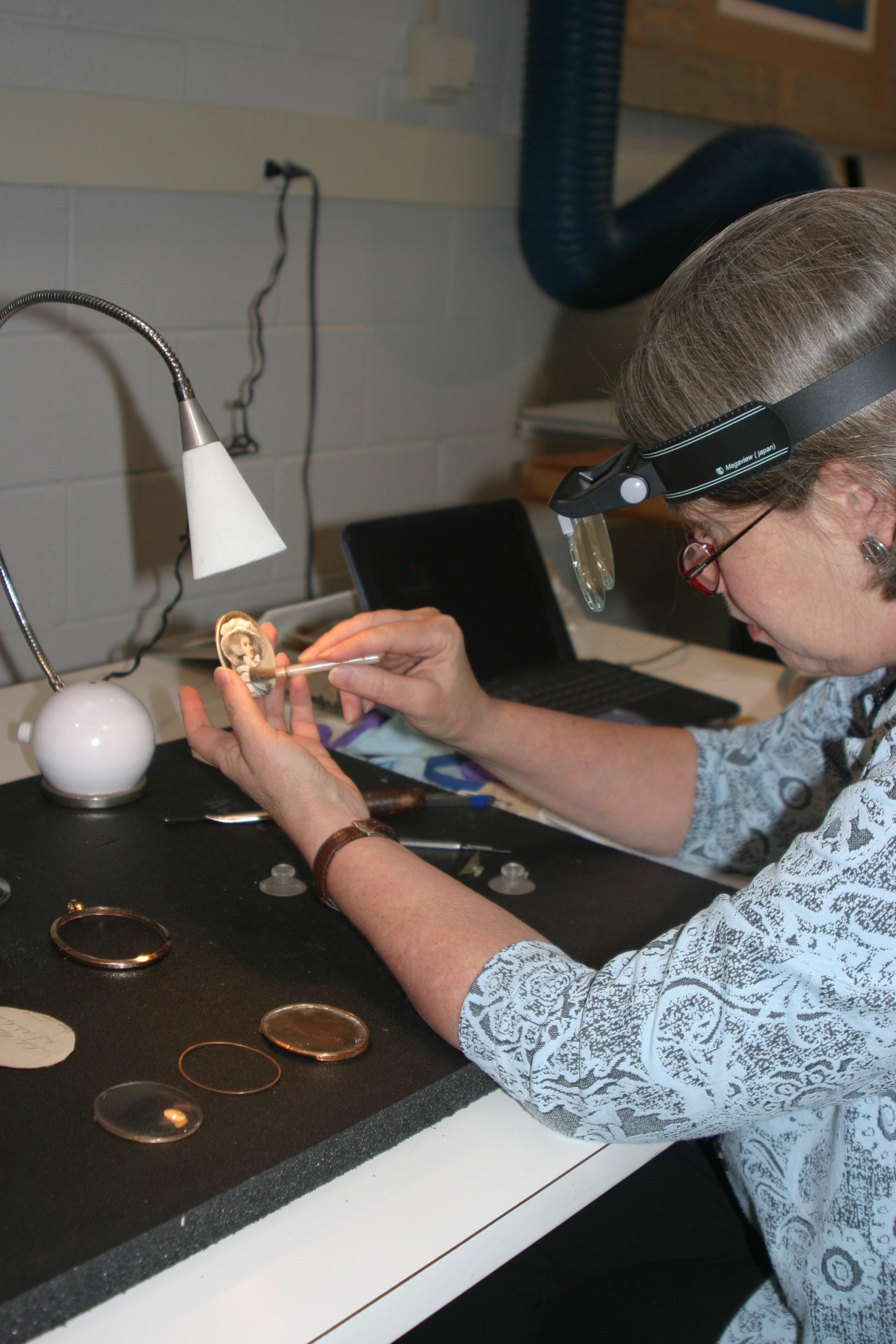 Carol Aiken clean one of the Milwaukee Art Museum's portrait miniatures. Photo credit: Terri White.
