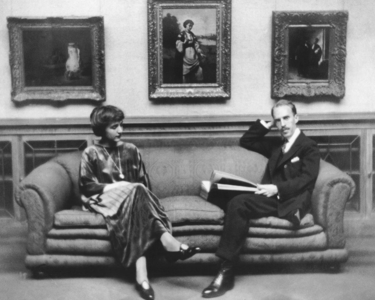 Man and woman sitting on a couch in front of a wall of framed art