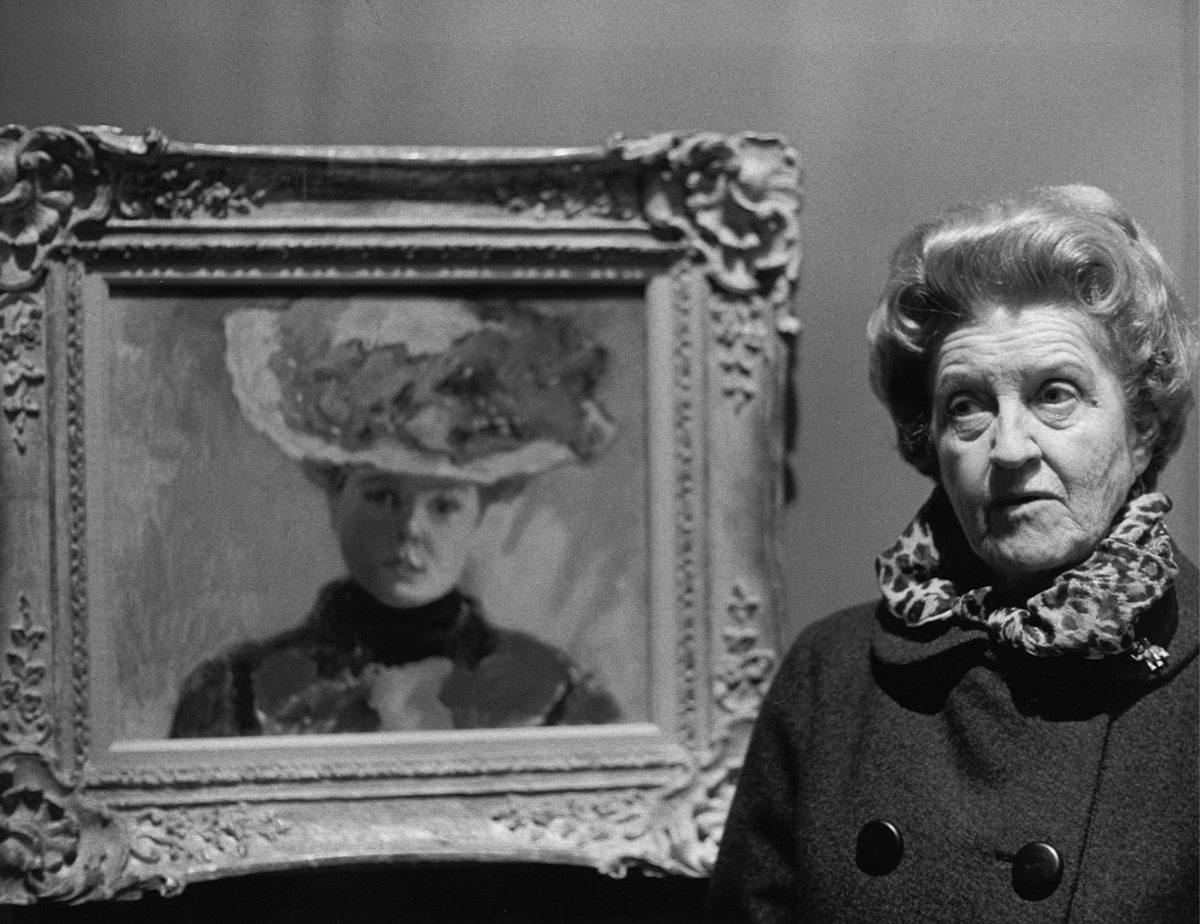 Older woman standing next to a portrait of a lady in a large hat