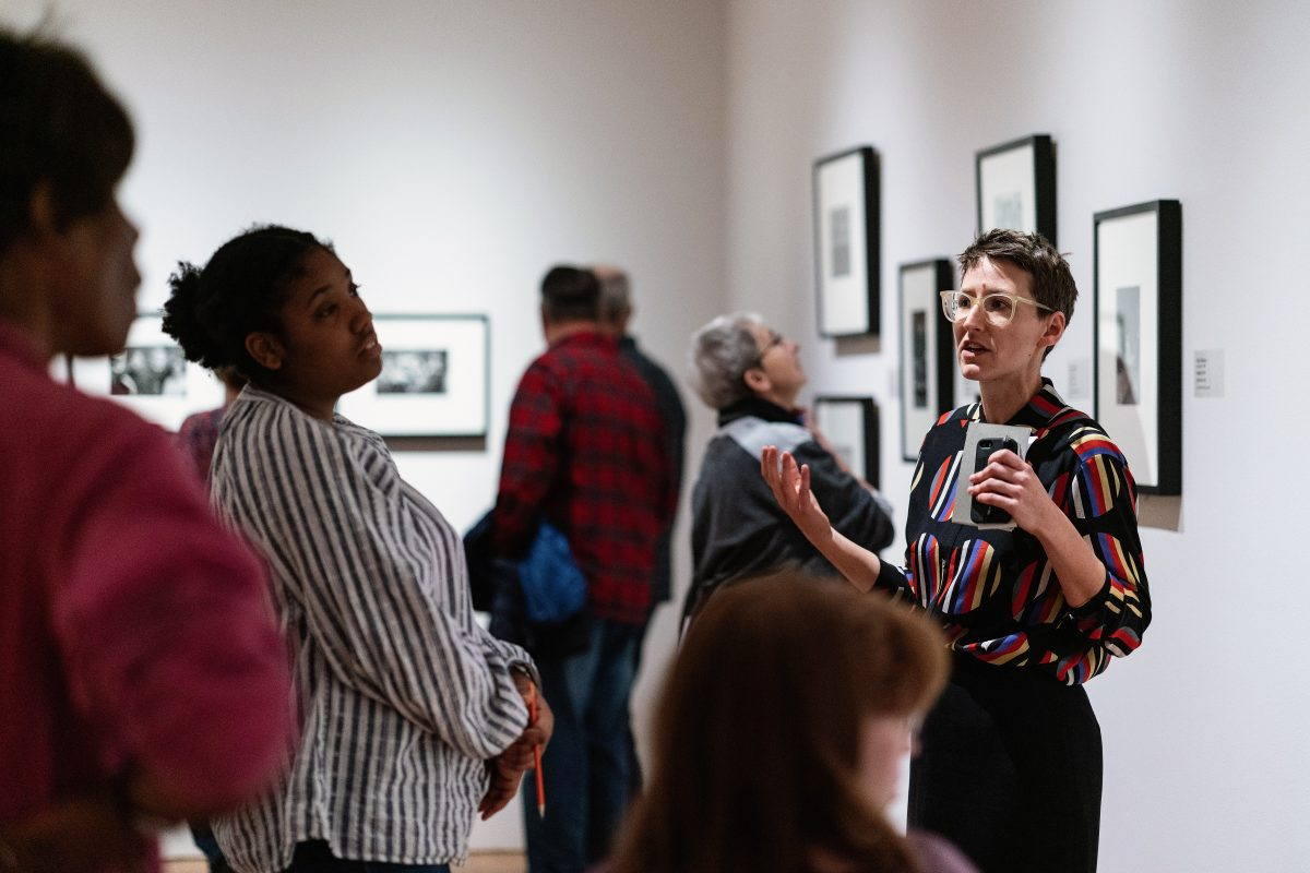 Ariel Pate giving a talk to a small group of people in front of a wall of framed art