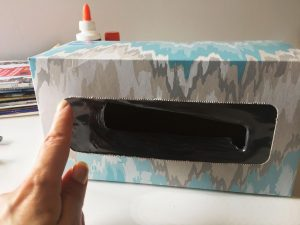 Hand pointing to the corner of a large tissue box