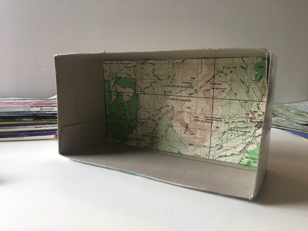 Tissue box with the top cut off and a map glued to the back
