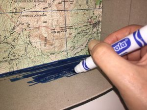 Large tissue box with a map glued to the inside and a hand coloring the bottom with a blue marker