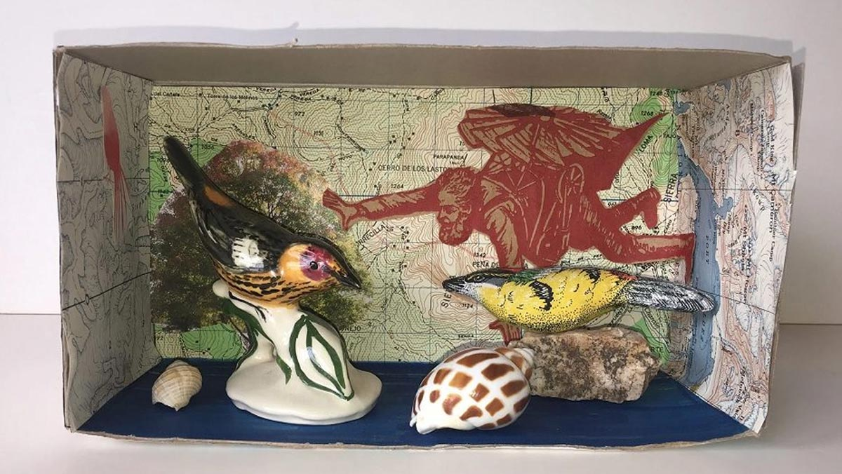 Shadowbox with map background, cutouts, bird figures, and shells