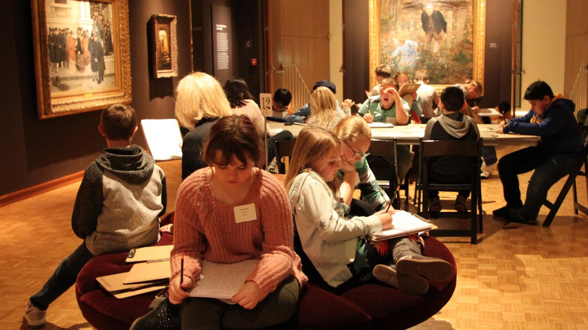 Children sitting in the Museum gallery writing