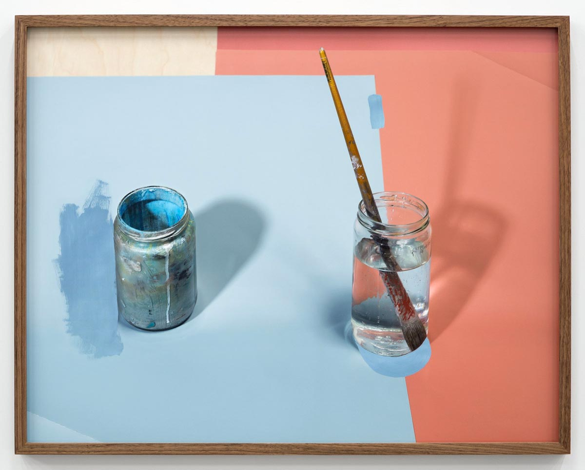 Two glass jars, one with paint and one with water and a brush