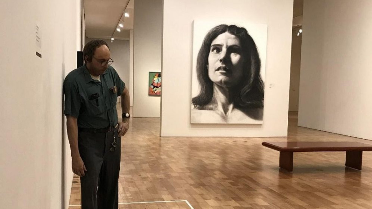 Lifelike Janitor sculpture leaning against a wall and a black and white portrait drawing of a woman