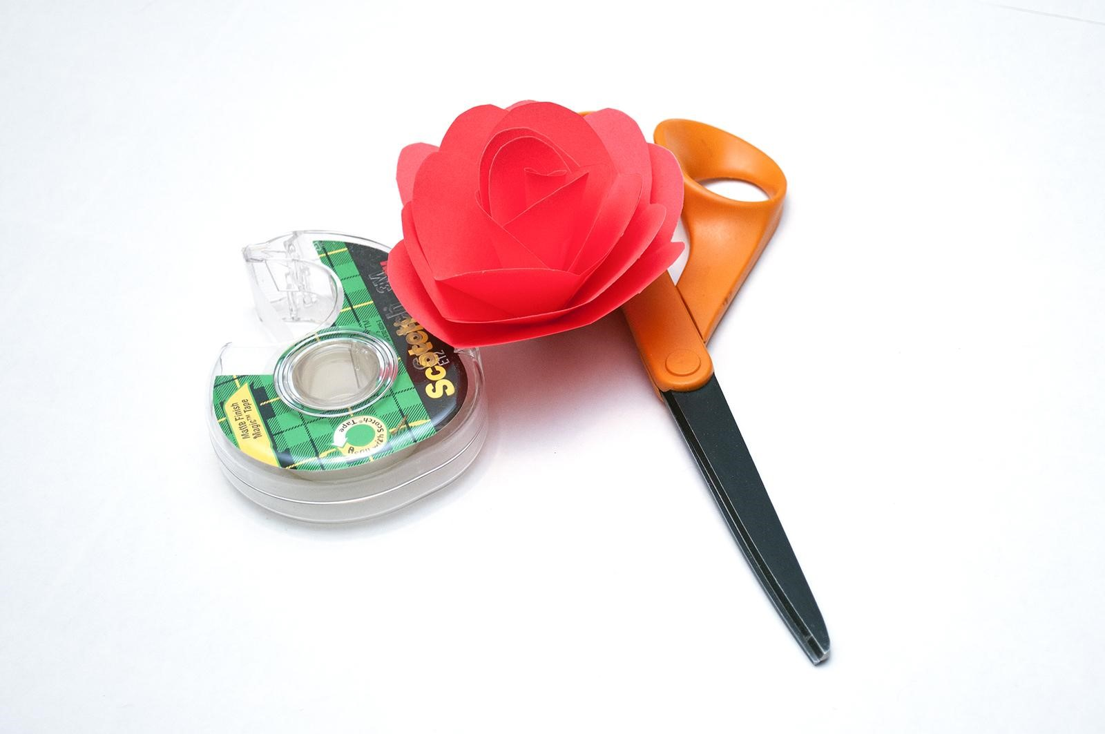Red paper rose sitting between scissors and a tape dispenser
