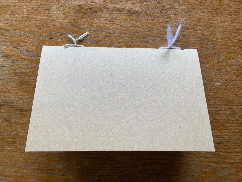 Pieces of paper folded in half and tied together with string and twist ties