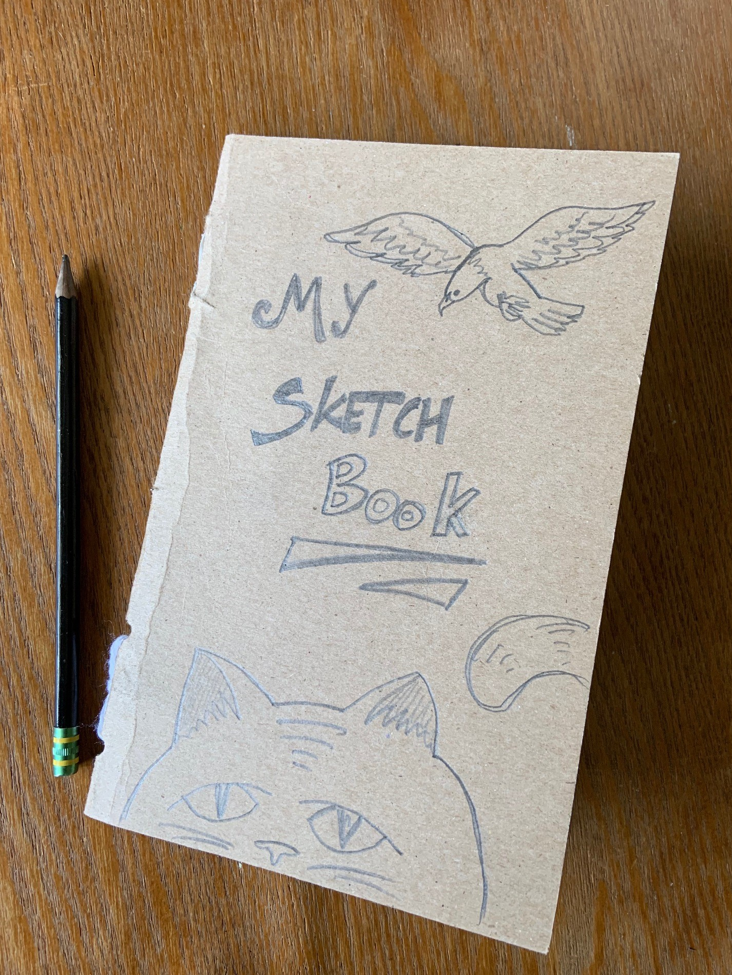 Homemade sketchbook with a bird and the top of a cat's head drawn on the front