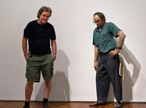 Older visitor standing next to a lifelike Janitor sculpture