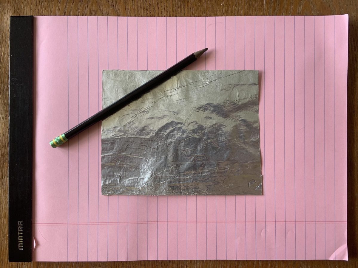 Large pink legal pad with a pencil ad square piece of foil on top