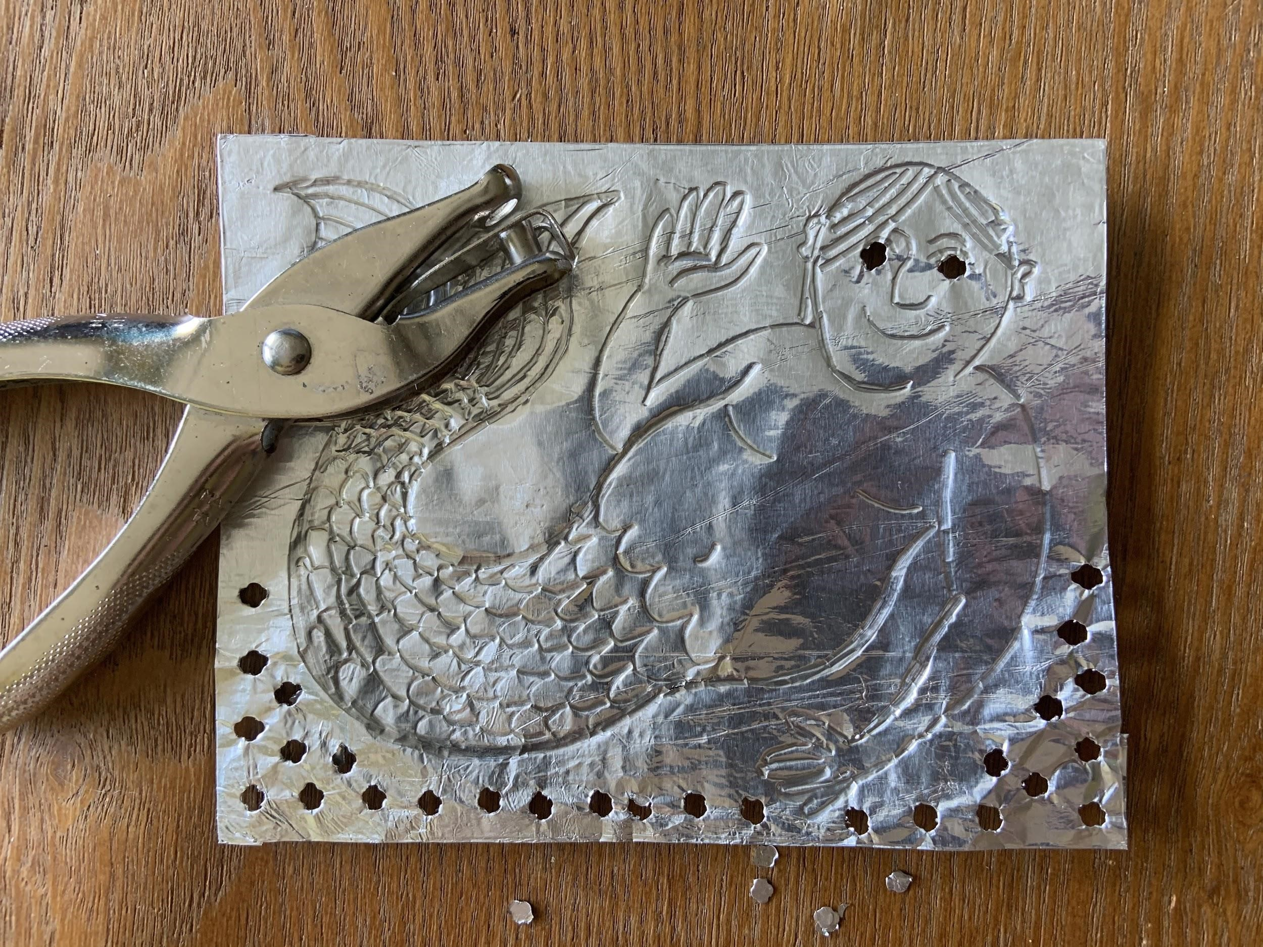 Mermaid embossed in a piece of foil with holes punched along the outside