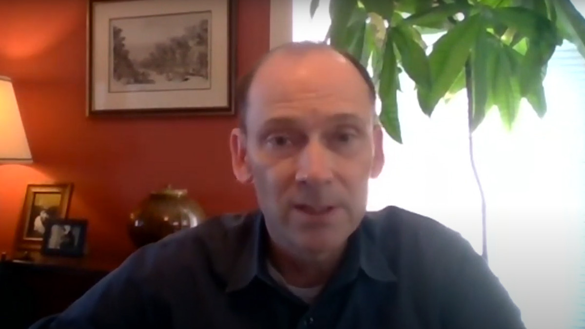Man talking to the camera in his home office