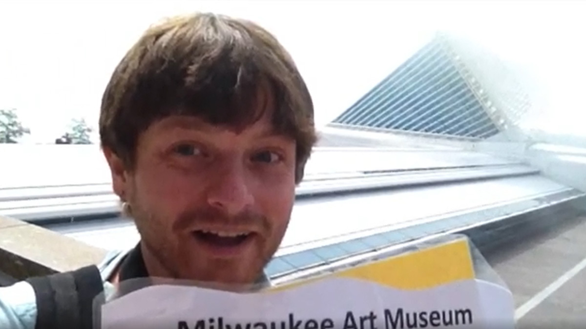 Man holding up a Milwaukee Art Museum sign in front of the Museum