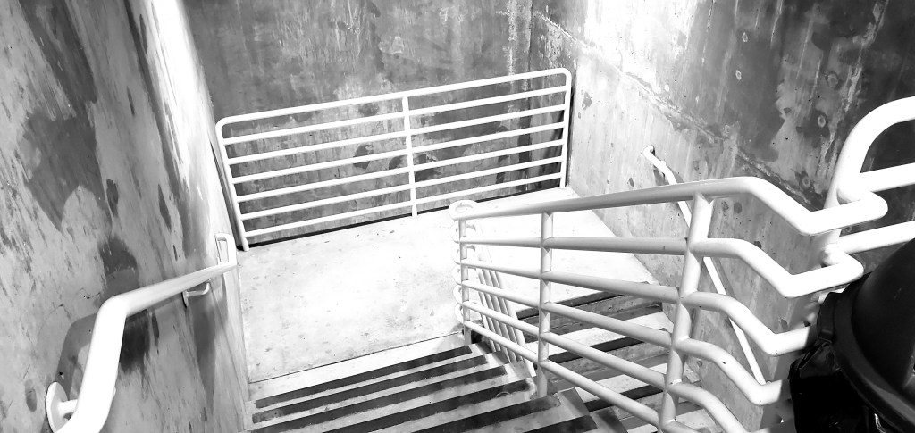 View going down stairs with metal railings