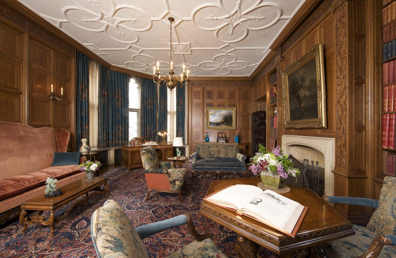 Elegant room with velvet furniture, art in gold frames, and a chandelier