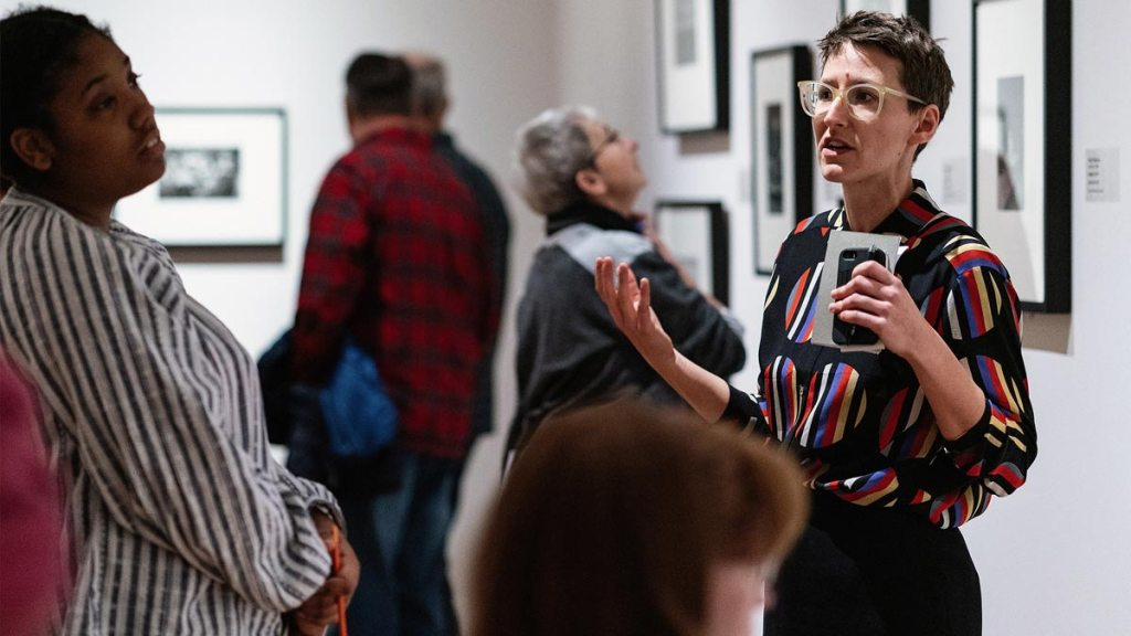 Woman in short hair and glasses talking to a small group of people about art