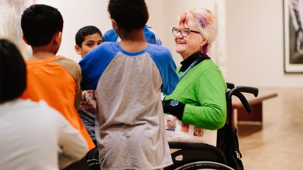 Woman with short blonde hair and a bright green top sitting in a wheelchair talks to a small group of young boys at a Museum