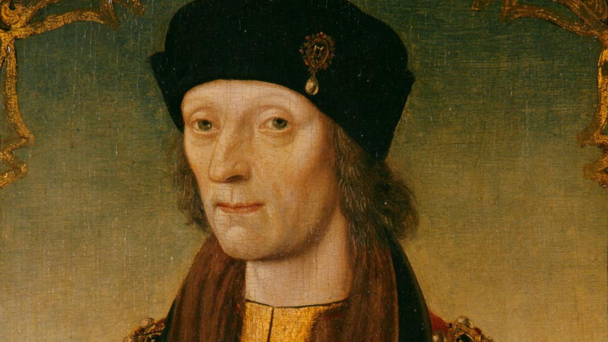 Man with medium-length hair wearing a black hat and a red and yellow robe