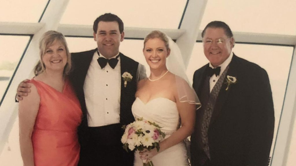 Bride and groom standing with a set of parents in the Museum; Krei family