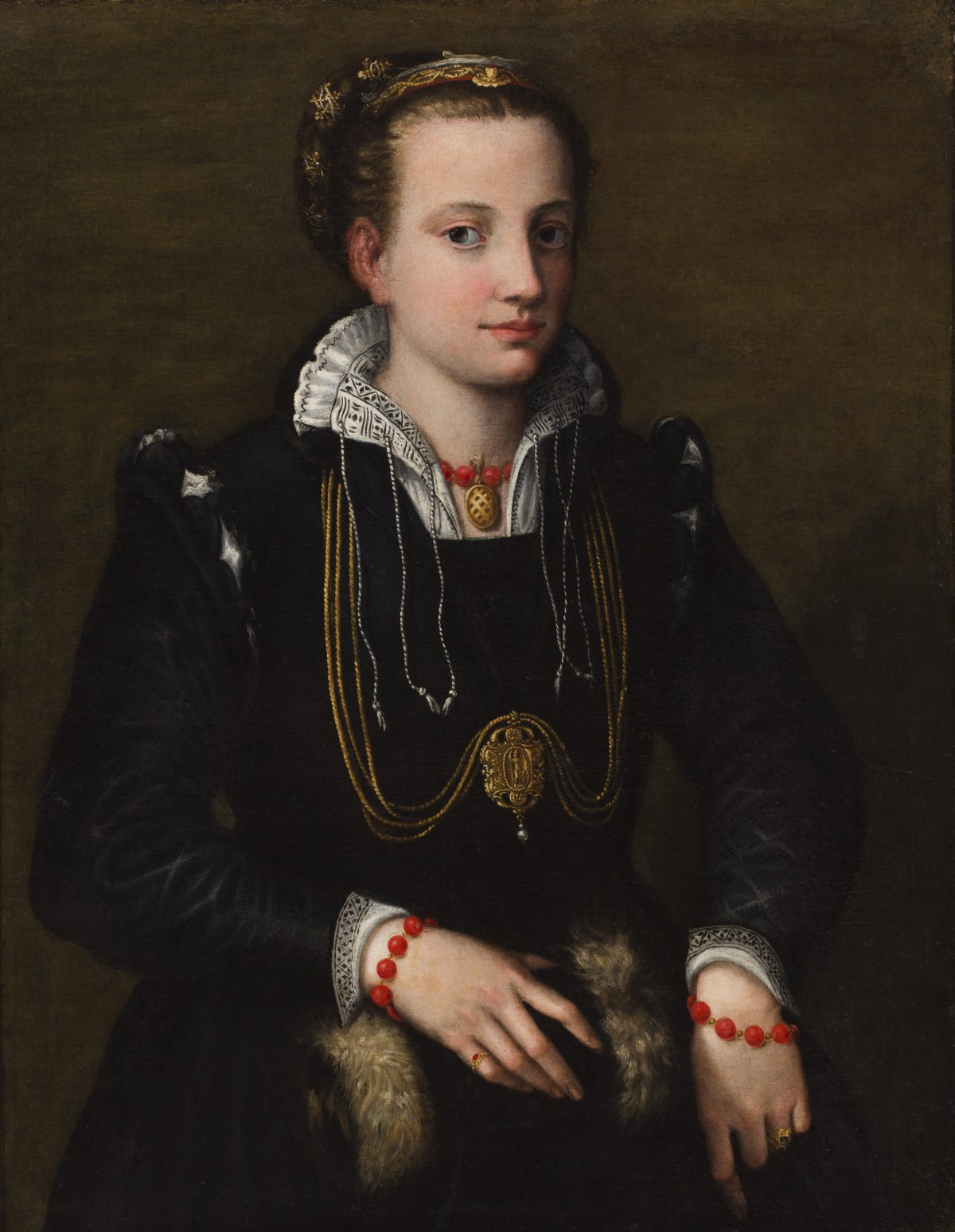 Portrait of a sitting woman with hair in a decorated bun and wearing a long dark robe