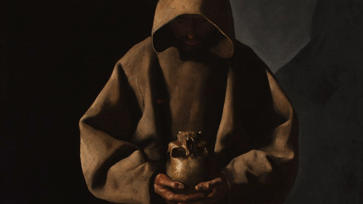 Man in brown hooded robe looking down at a skull in his hands