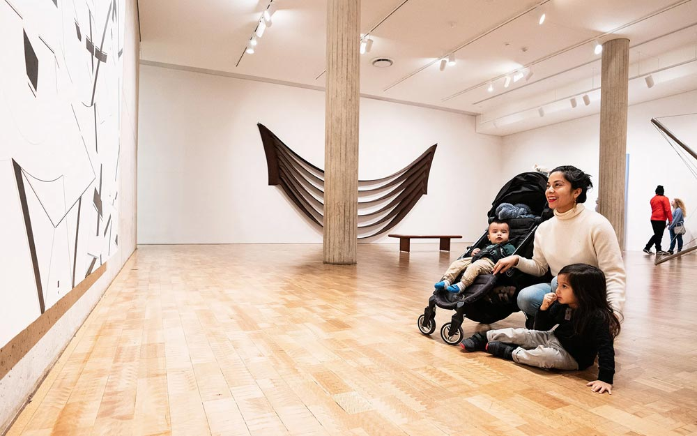 Woman and her small children looking at art