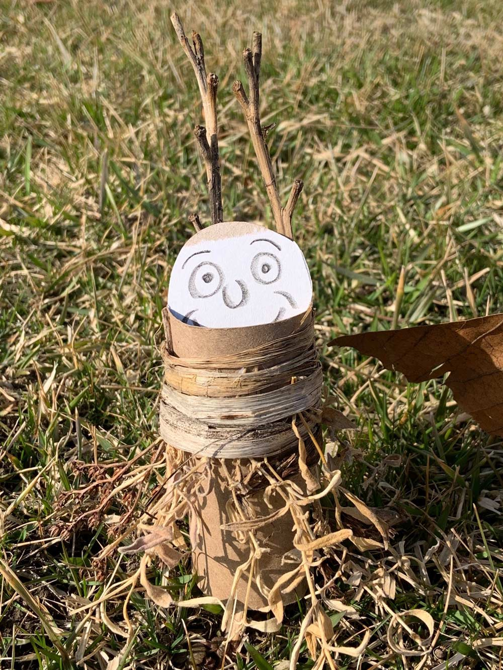Closeup of an owl made from a toilet paper roll, branches, and cardbaord