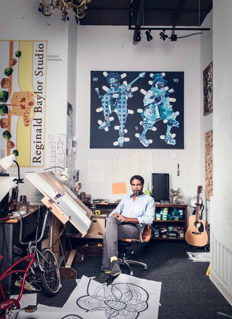 Man sitting in a room with art drafts on the floor, a bicycle in the corner, and paintings on the walls